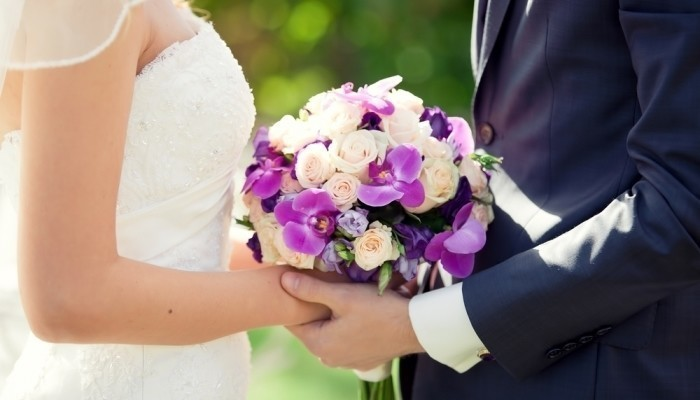 couple getting married holding bouqet of flowers