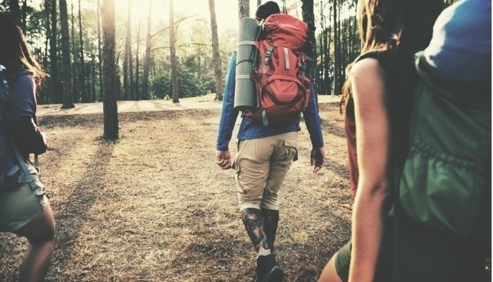 backpackers walking in forest