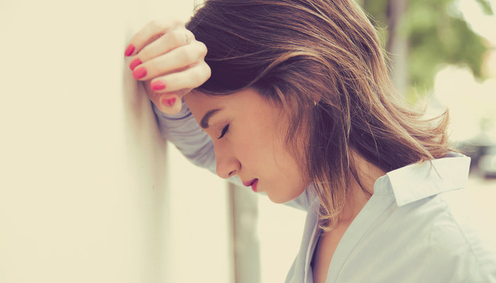 Stressed woman leaning against wall