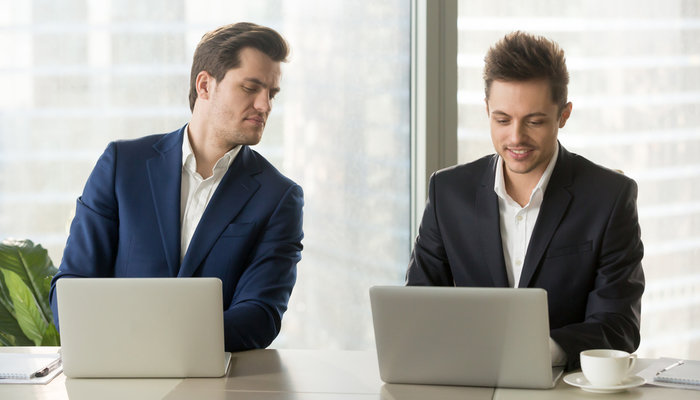 Curious, jealous businessman peering over coworker's laptop