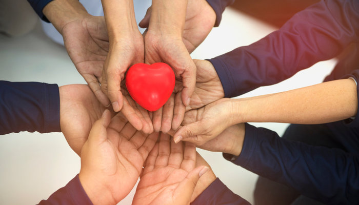 Group of hands holding red heart