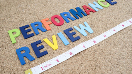 Letters spelling 'performance review' and tape measure