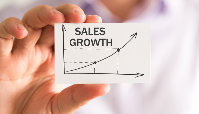 Businessman holding card with sales growth chart