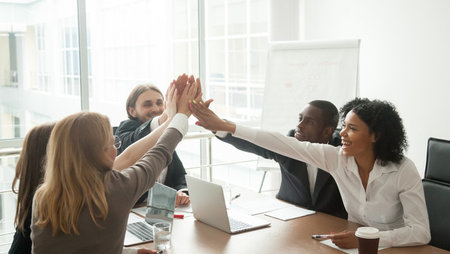 Group of happy employees giving each other high fives in meeting room