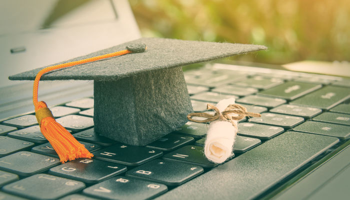 Mortarboard and diploma on laptop