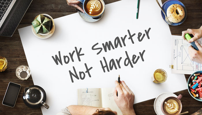 A group of people working together and sitting at a table with a sheet of paper that says 'work smarter, not harder'