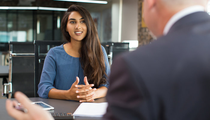 Smiling young woman attending a job interview with an older male HR manager
