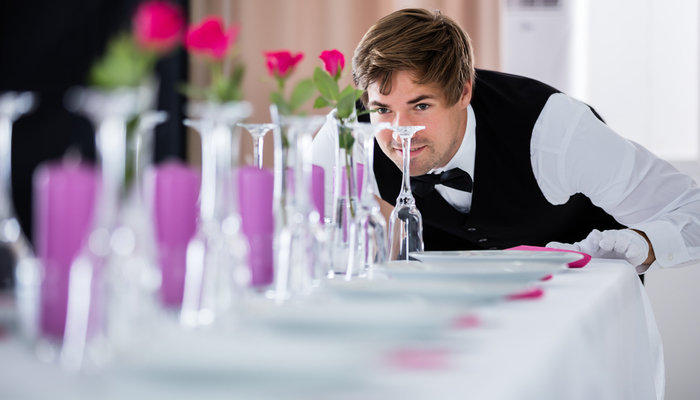 Young waiter looking at a table arrangement
