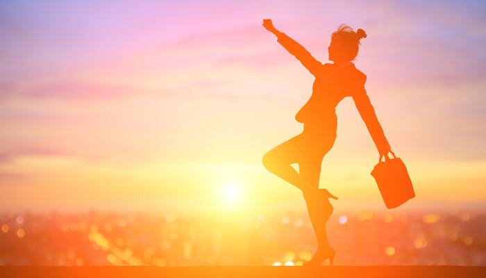Silhouette of an excited business woman standing in front of a sunset