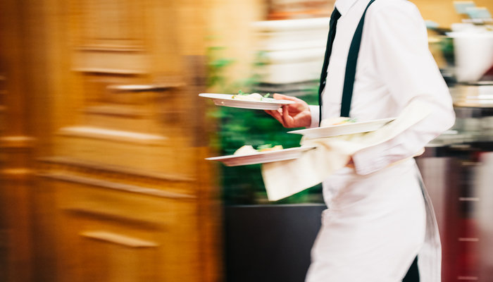 A restaurant server walking and carrying plates