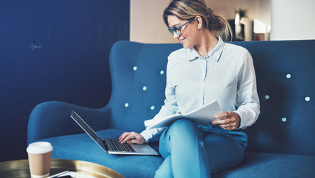 Smiling, young business woman sitting on a blue sofa and working on her laptop