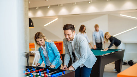 A group of coworkers playing foosball and billiards in office break room