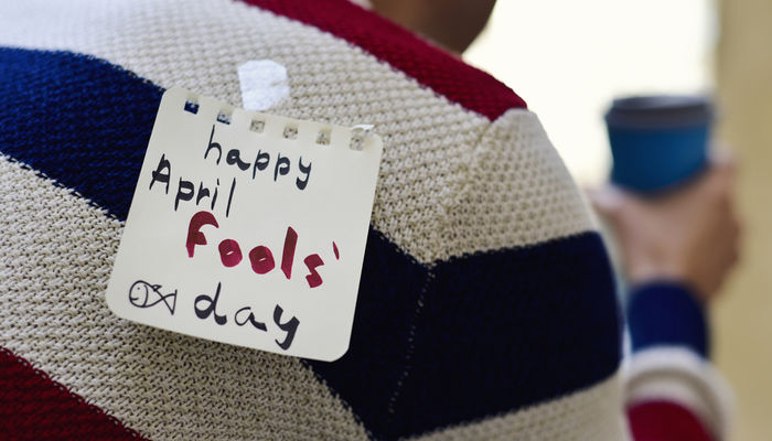 Close-up of a sticky note that says 'Happy April Fools' Day' stuck on a man's back