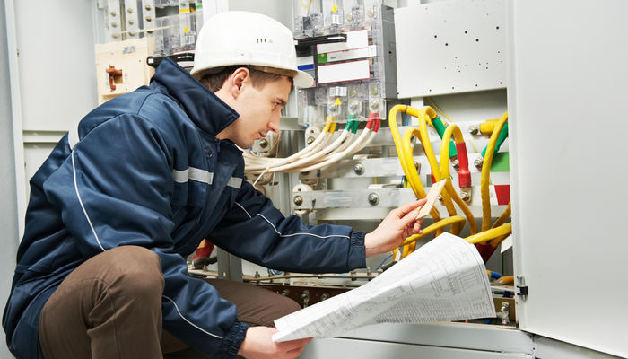 An electrician checking cabling and blueprints