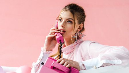 A young woman speaking on a pink landline telephone