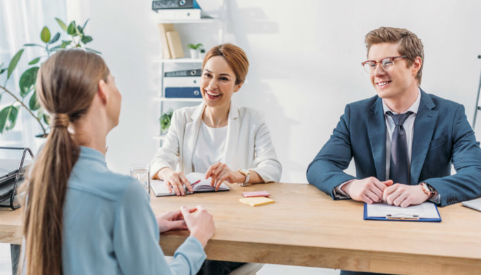 Two hiring managers interviewing a young woman in a modern office