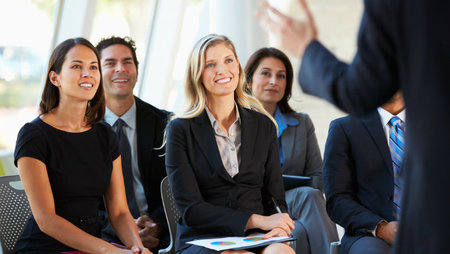 A group of smiling people listening to a speaker at a seminar