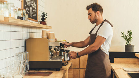 A male barista wearing a brown apron and making coffee