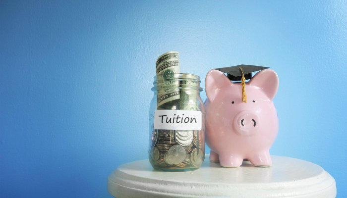 A piggy bank wearing a mortar board and a glass jar labelled 'tuition' standing on a white table against a blue background