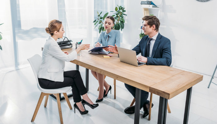 Two hiring managers interviewing a woman in a modern office