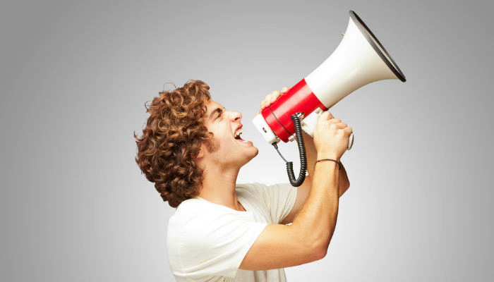 A young man with curly hair shouting through a megaphone