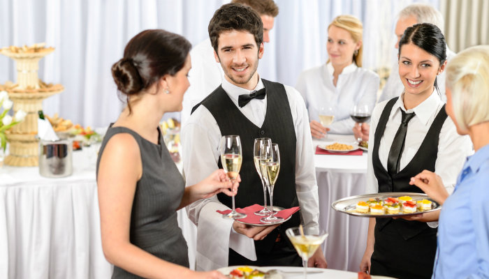 Two waiters offering champagne and canapés to guests at a catering event