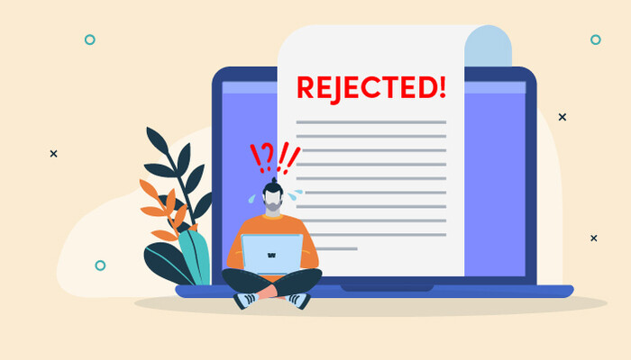 Illustration of a panicked man sitting in front of a large laptop and rejection letter