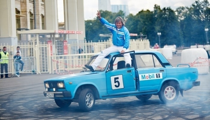 stunt driver sitting on top of car